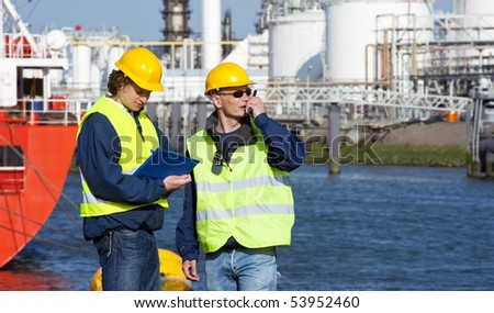 Two dockers during a routine inspection of an industrial harbor