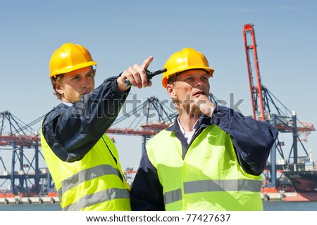 Two dockers in discussion, in front of a large industrial harbor