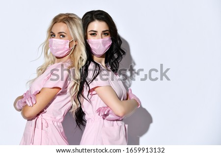 Two doctors in pink scrubs, disposable gloves and medical masks are posing isolated on white. Medical staff, cosmetologist, tattoo artist, hairdresser. Beauty. Foto d'archivio ©