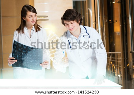 two doctors stand near glowing table discussing. projected objects on a desk