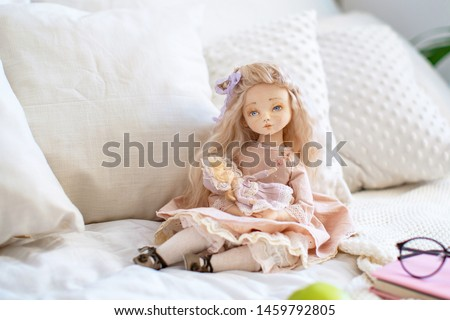 two dolls made by hands from textiles are very similar to living people. designer dolls. sitting on the bed. creating dolls for the new year holiday.doll mom with a little baby. mother's daughter game