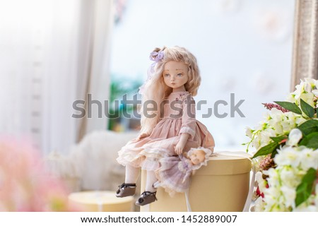 two dolls made by hands from textiles are very similar to living people. sit on boxes with presents. creating dolls for the new year holiday. doll mom with a little baby. mother's daughter game