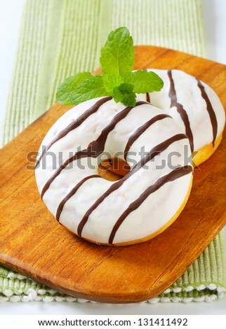 two donuts with sugar glaze on the wooden cutting board