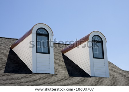 Two dormers on a roof against blue sky - stock photo