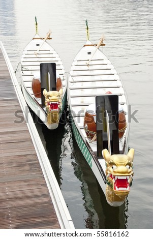 Two dragon boats tied up at jetty ready to race