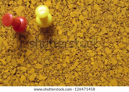 Two drawing pins on an empty corkboard
