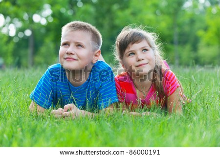 Two dreaming children are lying on the grass