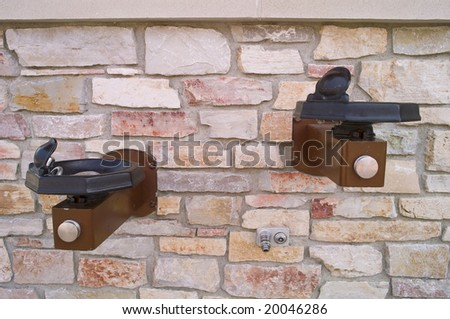 Two drinking fountains and a hose faucet on a brick wall