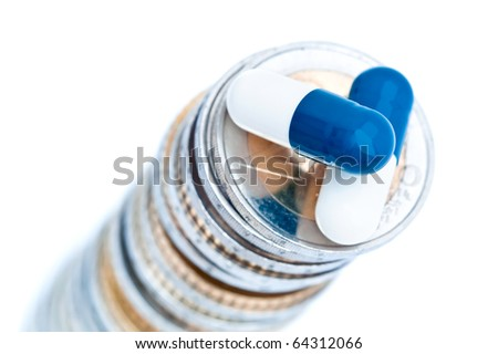 Two drug capsules or pills on tall stack of European coins,, isolated on white background.
