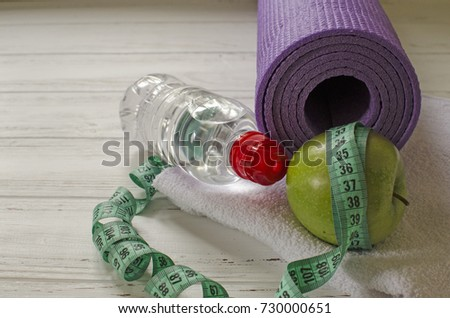 Two dumbbells, bottle of water, green apple and peppers, centimeter on white wooden background with space  for text