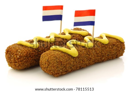 "Two Dutch snacks called ""kroket"" with mustard and  Dutch flag toothpicks on a white background"