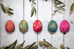 Two Easter symbols: eggs and olive twigs. Five coloured eggs with olive twigs around them on a shabby chic wooden table.