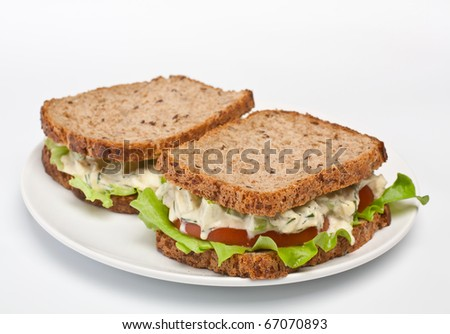 two egg salad sandwiches on brown toasted bread