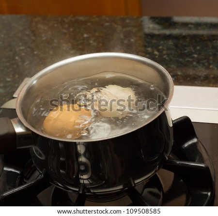 Two eggs in boiling water in stainless steel pan on gas hob