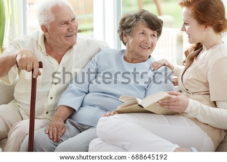 Two elder people are looking at smiling nurse who reads book in common room #688645192