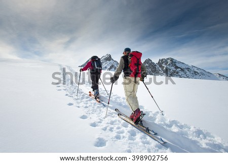 Two elderly alpine skiers climb on skis and sealskins