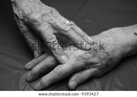 two elderly hands touching