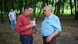 Two elderly people talking in a park. Oldman with plastic cup listening to friend