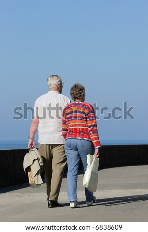 Two elderly people walking together