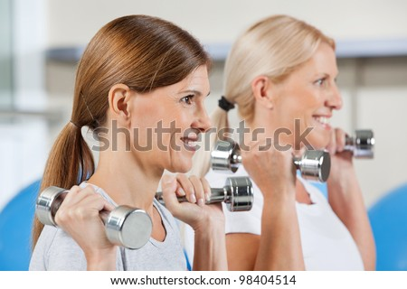 Two elderly women exercising with dumbbells in fitness center