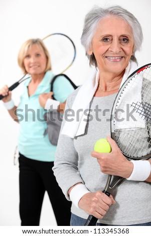 Two elderly women playing tennis - stock photo