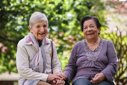 Two elderly women sitting on bench in park holding hands smiling happy life long friends enjoying retirement