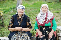 Two elderly women sitting outdoors