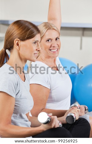 two elderly women working out with dumbbells in gym