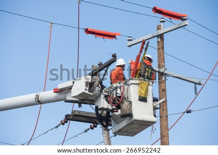 Two electric power workers hover in a bucket as they make repairs.