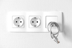 Two electric sockets and internet outlet built into a single unit on the white wall. Indoors, textured stucco, simple and elegant design.