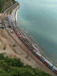 two electric trains go on the railroad tracks along the sea towards each other. One train is very long, its cars are hidden behind a mountain on the horizon. The second train crosses a mountain river