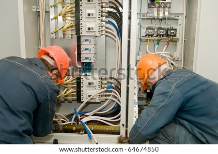 Two electricians working on a industrial panel mounting and assembling new wiring