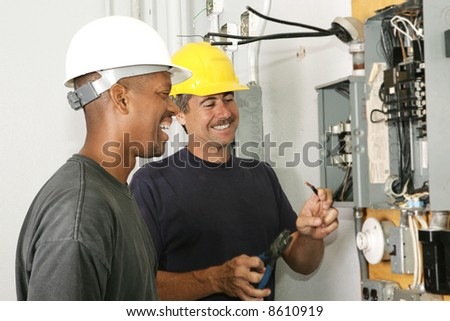 Two electricians working on an electrical panel together.  Actual electricians performing work according to industry code and safety standards. - stock photo