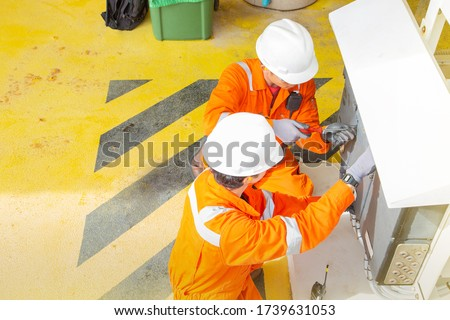 Two electricians working on offshore oil and gas production platform to maintenance electrical system on platform. stock photo