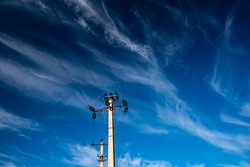 Two electricity pylons against dark blue sky with white clouds, space for text.