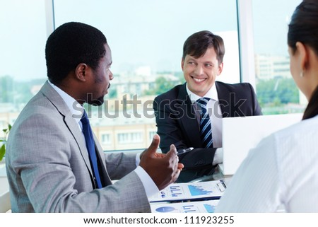 Two elegant businessmen communicating at meeting