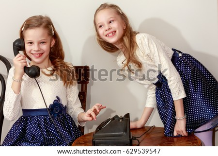 Two elegant girls sisters in beautiful dresses, talking on old phone. Retro style.Retro style. #629539547