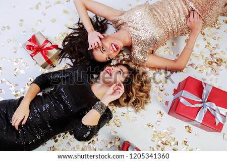 Two elegant  gorgeous women in trendy sequin dress lying on white floor with shining golden confetti and red gift boxes . Celebrating new year or birthday party.