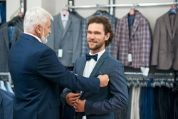 Two elegant men coming fashion boutique on shopping. Concept of picking up fashionable costumes.