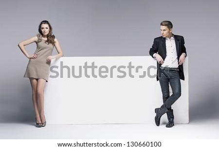 Two elegant people next to big white board