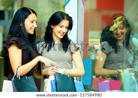 two elegant women look in clothes store showcase - stock photo