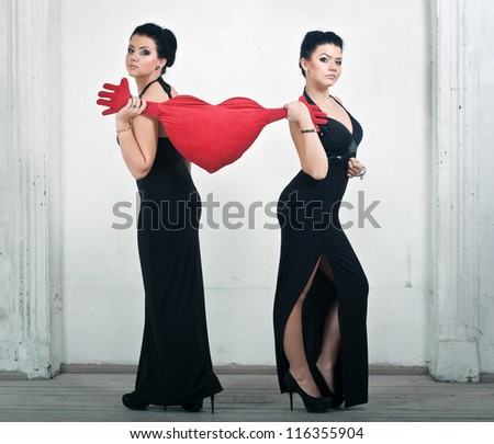 Two elegant women\'s sister pulled a pillow in the shape of heart in different directions.