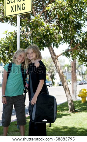 Two Elementary Age Kids with Backpacks at the School Crosswalk. - stock photo