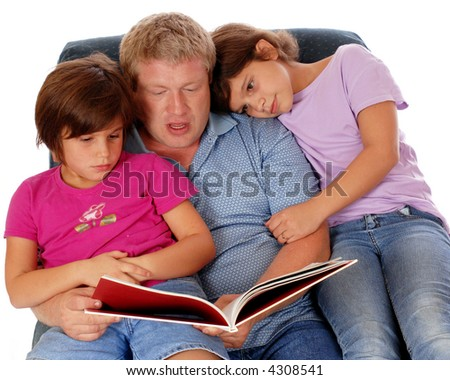 Two elementary-aged girls cuddled with their dad in an overstuffed chair while they listen to a story.  Isolated on white.