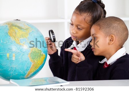 two elementary school students looking at globe