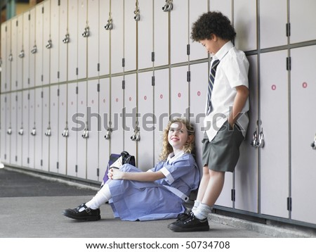 Two elementary school students waiting by school lockers