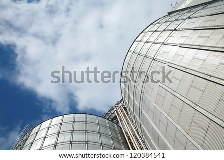 Two elevators under a blue cloudy sky