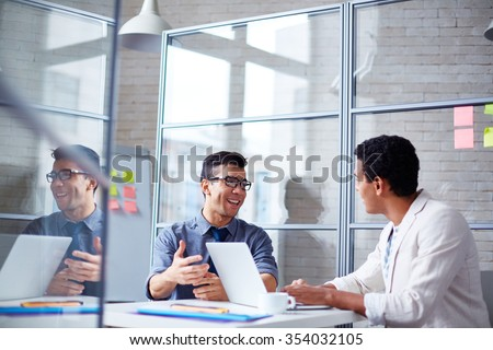 Two employees discussing data at workplace in office