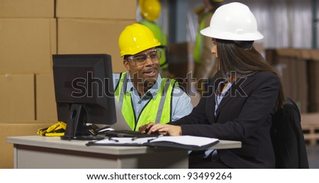 Two employees working together in shipping warehouse