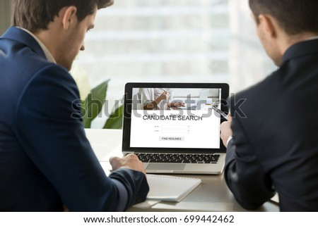 Two employers look for professional staff on laptop online, hr managers discuss new candidates searching for job on web service, choose best resume to invite seeker at interview, close up rear view